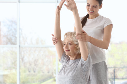 A woman doing arm strengthening exercises with a female phyiotherapist