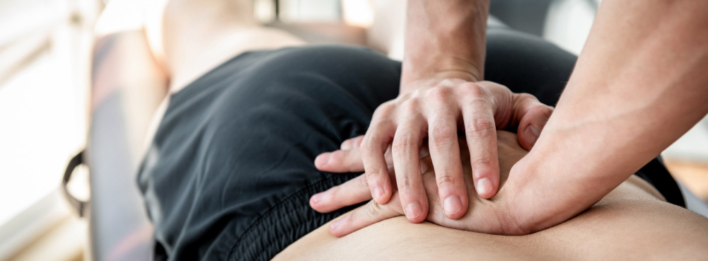 Close-up of a physiotherapist's hands treating a patient with lower back pain