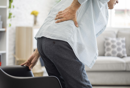 An older man attempts to sit while experiencing lower back pain