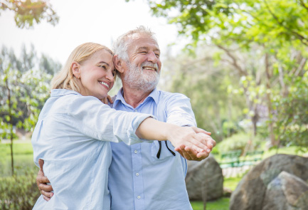An active elderly man dances with a woman outside