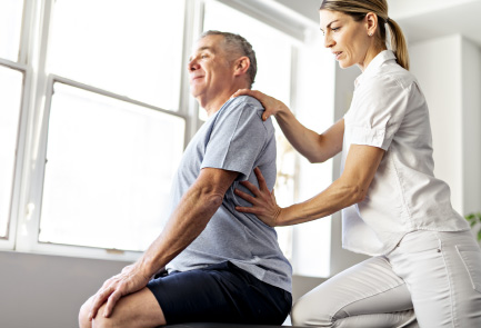 Woman physiotherapist treats a man for back pain
