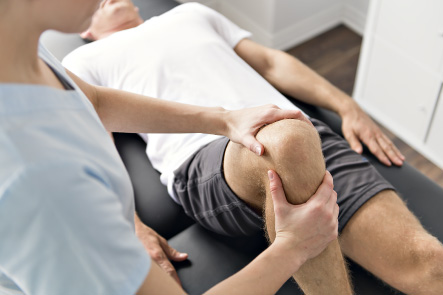 A sports physiotherapist inspecting her patient's injured knee