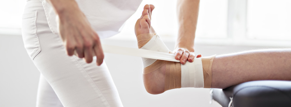 Sports therapist taping a patient's injured ankle