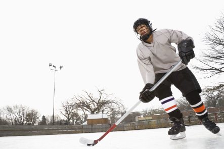 A hockey player practicing on an outdoor hockey rink