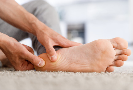 A man rubs his heel to relieve pain from plantar fasciitis