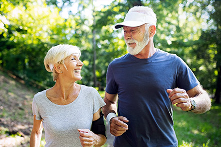 smiling mature couple running pain free with restored joints