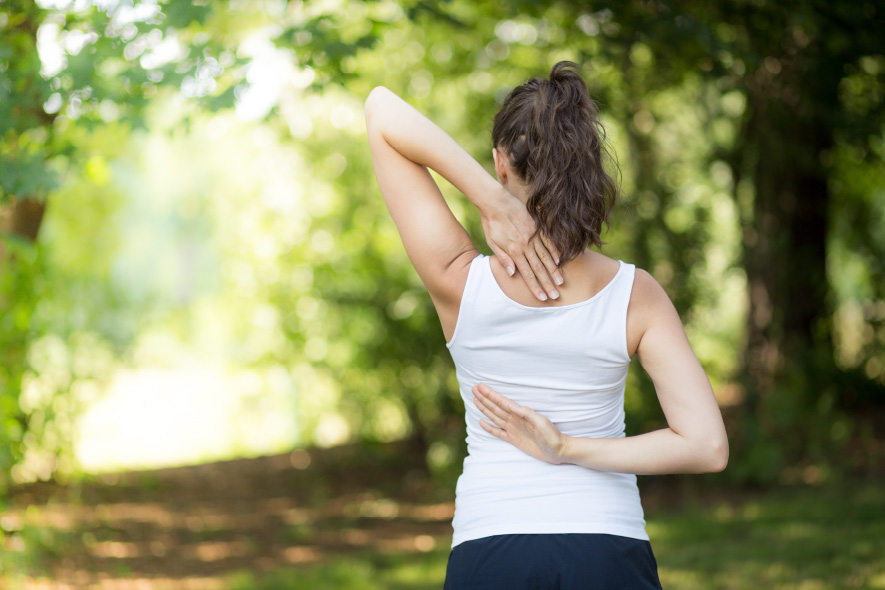 Woman with Idiopathic Scoliosis stretching in the outdoors