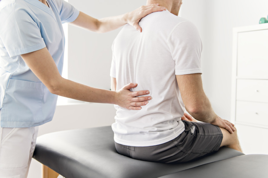 A physiotherapy therapist treating a fit man with scoliosis